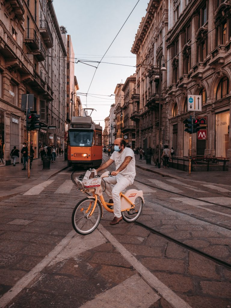 man in white shirt and white pants riding on bicycle on street during daytime